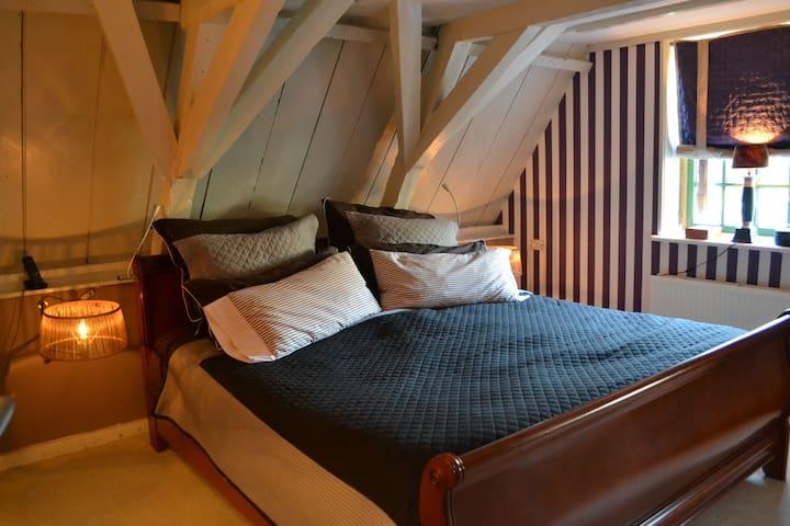 in de paarse kamer - die voorzien is van met de hand geschilderde paarse strepen - slaapt u op een luxe tweepersoons bed