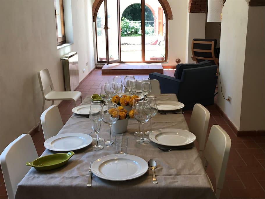 il tavolo da pranzo apparecchiato con bicchieri da prosecco, vino bianco e rosso; in toscana il vino è centrale!