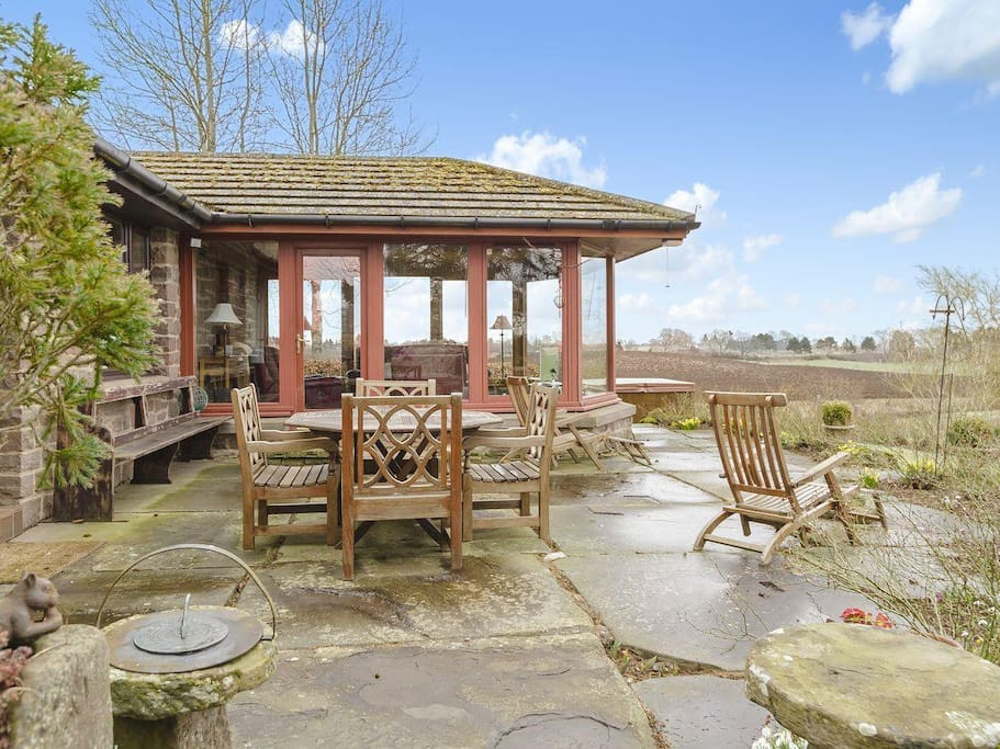 Outdoor dining area with views over private pond and Strathmore valley