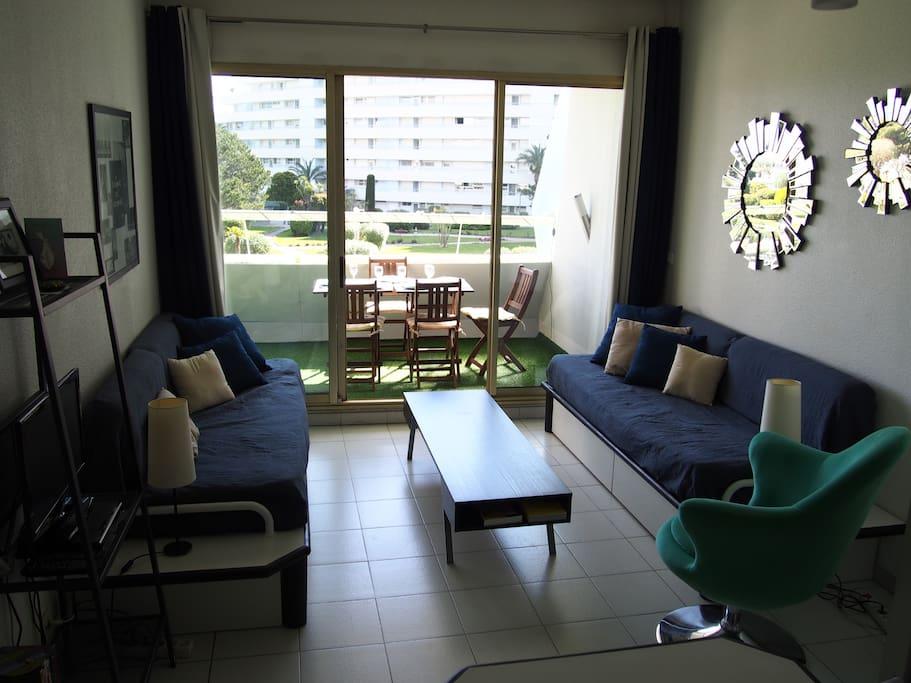 Le salon avec 2 lits simples et une vue mer/jardin