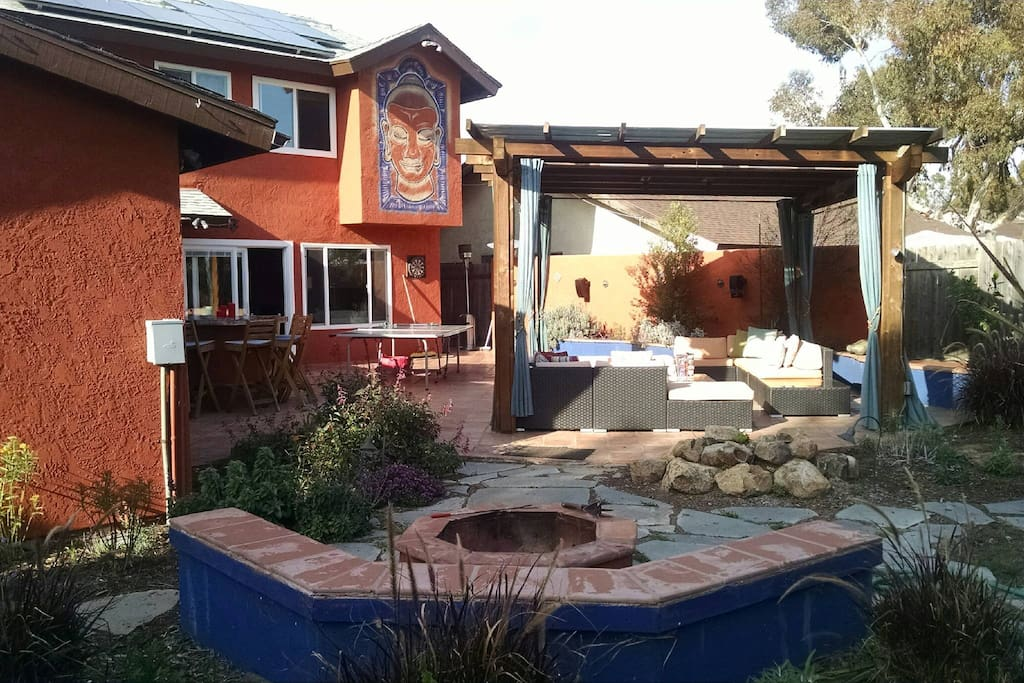 Gorgeous back yard with hot tub, firepit, grill, pingpong table, and seating