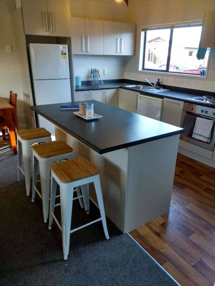 Fully equipped kitchen with seating at the kitchen table and also three bar stools at the bench.
