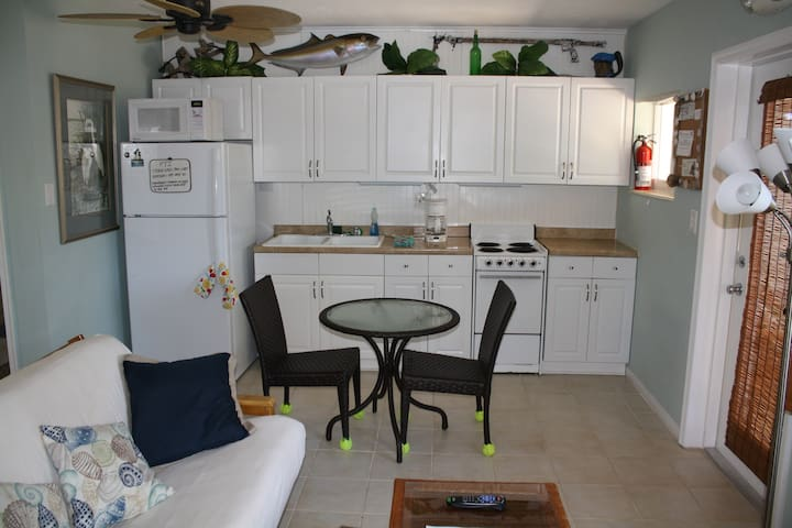 Kitchen with full size refrigerator with freezer, 4 burner stove, microwave. Additional gas BBQ grill outside.