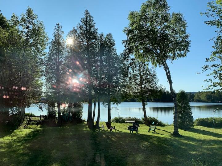 Chalet sur le bord d'un lac avec lever du soleil
