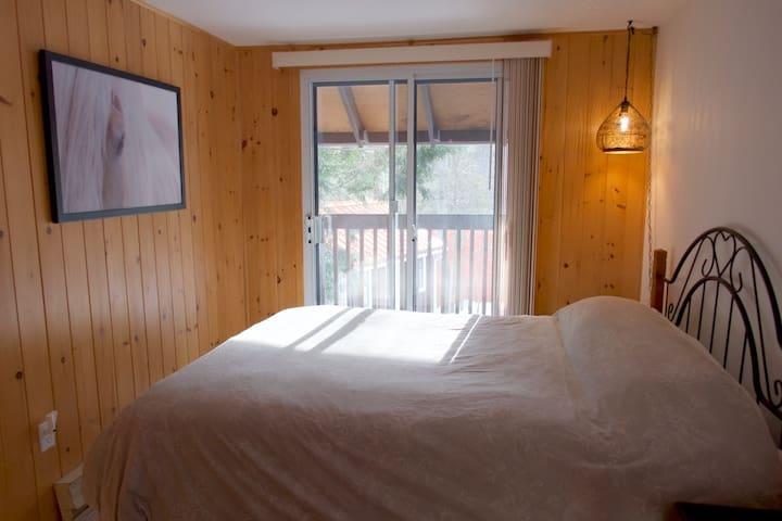 Chambre avec lit queen, balcon et salle d'eau attenante.