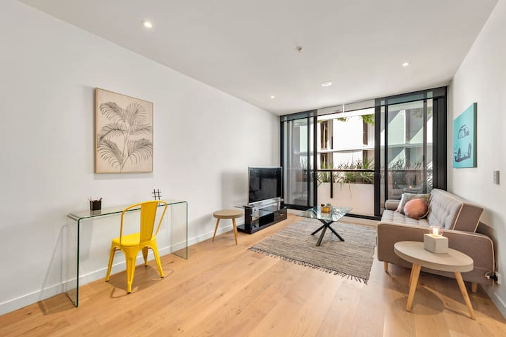 Beautifully decorated, open plan living room which flows out to the balcony. Comfy couch, stylish dining area, gorgeous hardwood floors and views towards the city (PS that TV has Netflix capabilities too!)