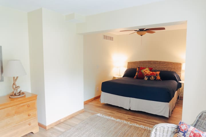 First floor master bedroom with king sized bed.  Sliding door to deck with lake and garden views.