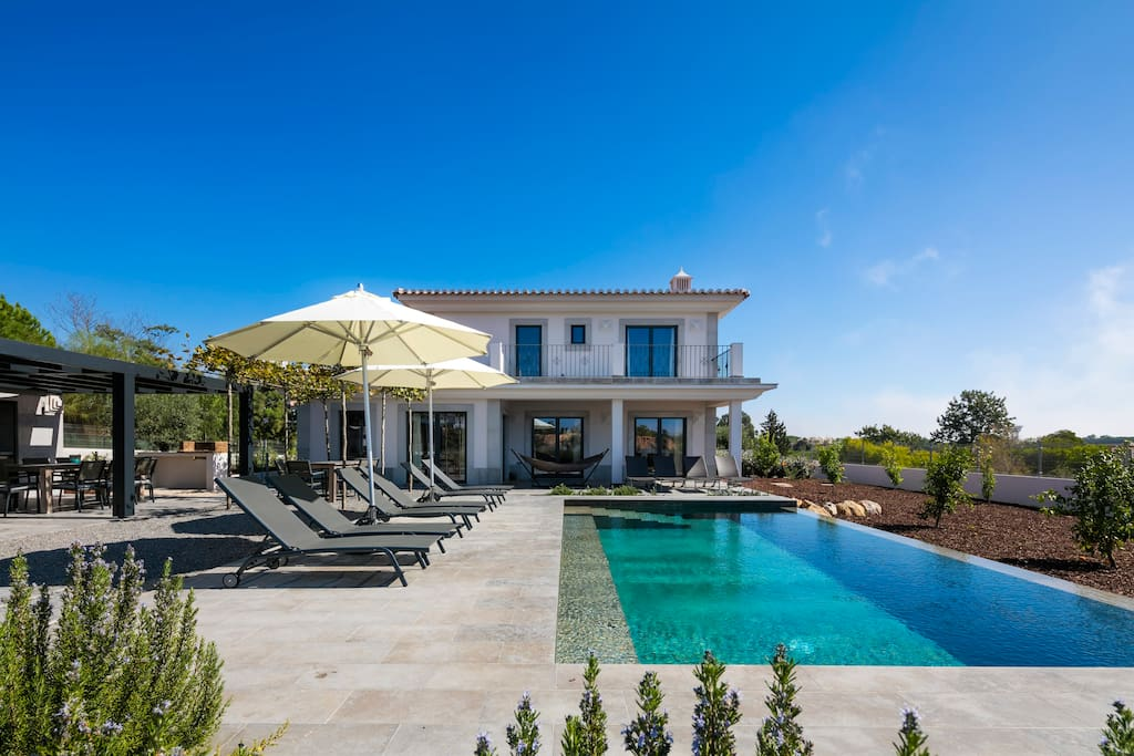 Inifinty pool and outdoor relax area with sunbeds, large outdoor fireplace and separate barbecue.