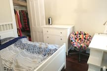 Middle room. with Queen bed, desk, chair, dresser, closet, small fan with a window that have the view on the back yard
