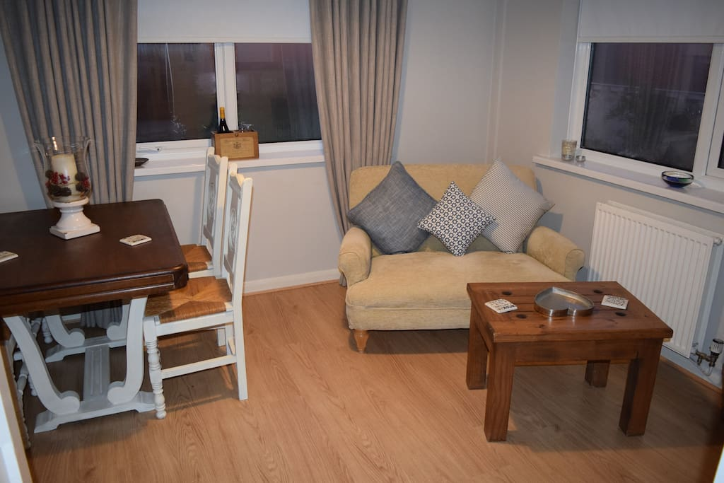 Living room with dinner table for four and digital TV.