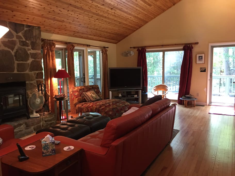 Sunny cabin in the woods features screened porch off living room with table and chairs.