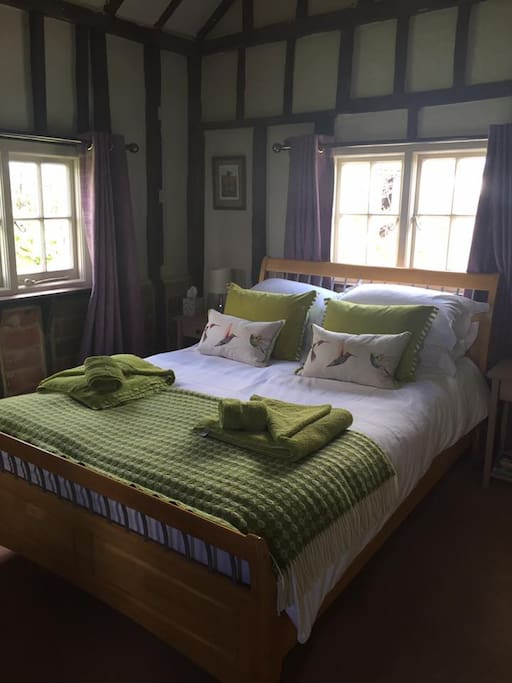 Fine linen, plenty of plump pillows and cosy throw on the bed opposite the open log fire. Extra radiator heating also available and underfloor heating in bathroom