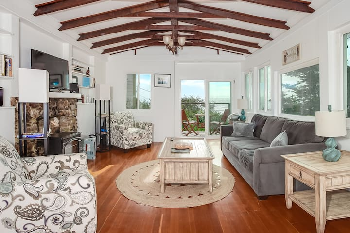 Living room windows open to the ocean below and the monarch butterfly trees across the street (feels like a tree house).