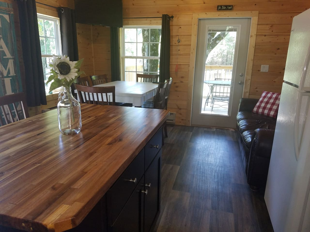 Comfortable leather couch and table seating for 9. Door opens to private deck overlooking wooded area.