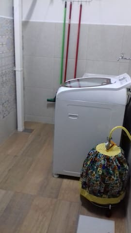 Área de serviço com máquina de lavar, tanque de louça e churrasqueira