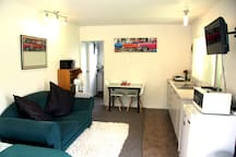 As you step into the studio, to your right is the kitchenette, tv, microwave, sofa to relax, dining table/chairs at end, and open door into bathroom,shower and toilet