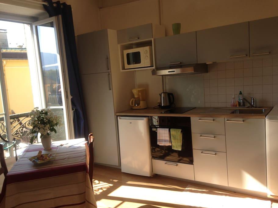 côté cuisine très fonctionnel : lave linge, four, plaques, réfrigérateur, hotte aspirante.