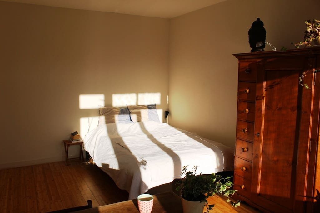 The sunny large bedroom with a comfortable bed