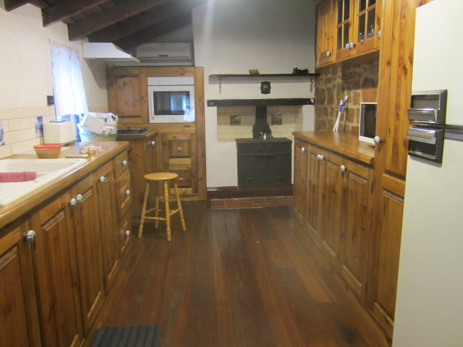 Spacious kitchen with wood stove, gas stove, electric oven & microwave