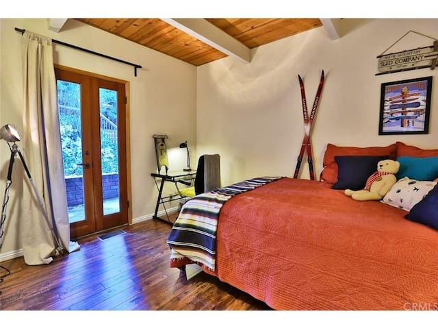 Main floor bedroom with queen bed. French doors lead to the outside front of the house