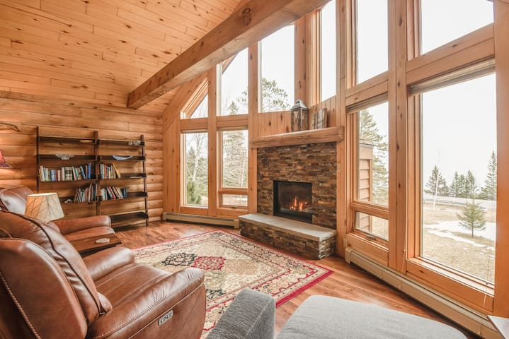 Main floor living room with floor to ceiling windows overlooking Lake Superior. A gas fireplace keeps the Lodge cozy and warm.