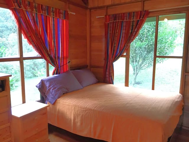 The master bedroom with double bed adjoins to the bathroom & living area, with views of the surrounding garden & mountains.