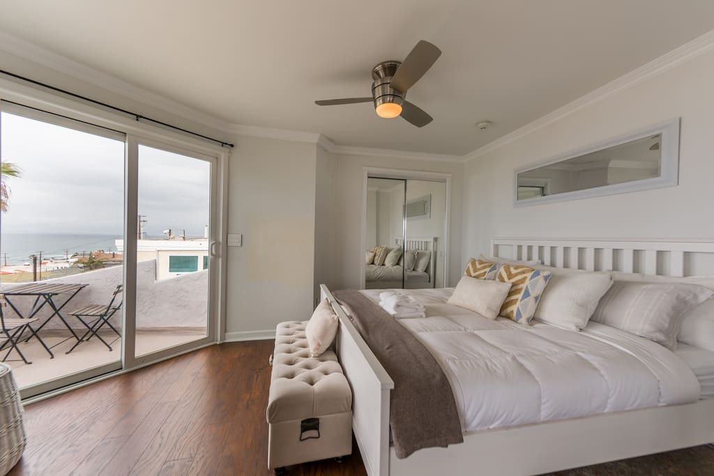 Master bedroom with king-size bed, TV, ceiling fan and direct access to balcony
