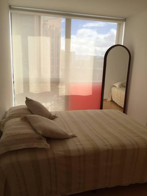 Comfortable bedroom with double bed and a mirror/Cómodo cuarto con cama doble y espejo de cuerpo completo
