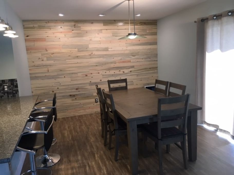 Dining room with plenty of seating for guests and beetle kill accent wall