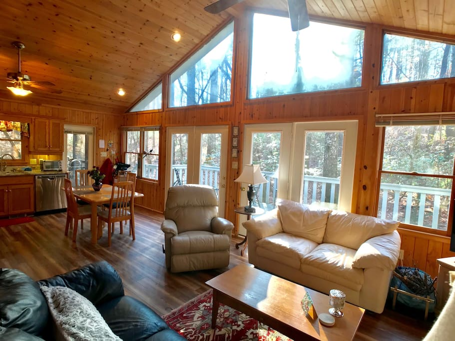 Sunlight pours in the open living/dining area with views of wildlife outside.