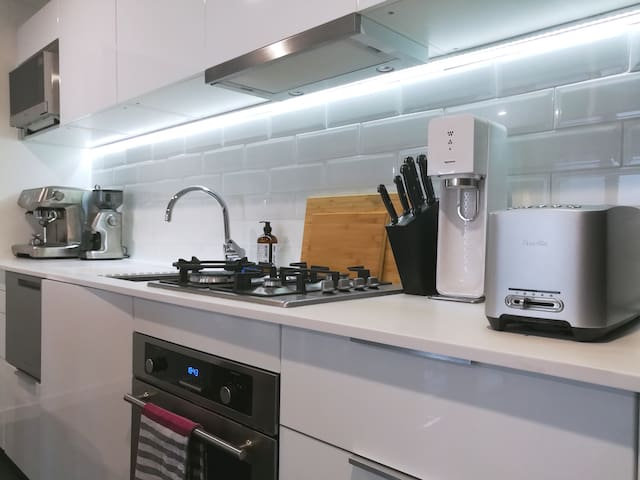 Fully equipped apartment kitchen, including fridge, washing machine, oven, gas stove, washing machine, sparkling water, and coffee machine.