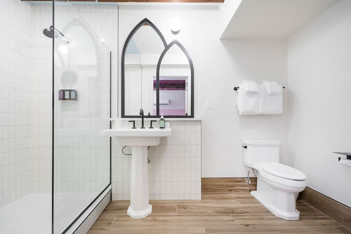 Unique white bathroom complete with cathedral mirrors and shampoo, conditioner, and body wash in the showers.