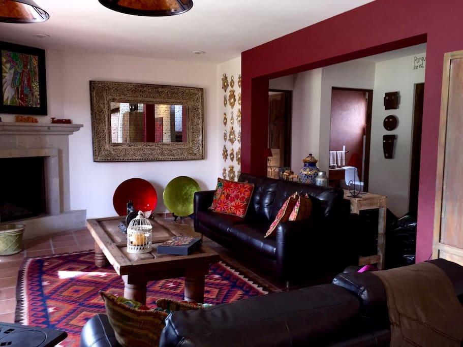 Sala con chimenea y con una maravillosa vista al jardín privado de la casa