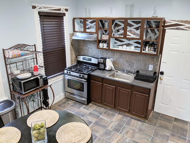 Shared Space- Fully Functional Kitchen/Dining Area Features: Stainless Steel Refrigerator that dispenses Filtered Water and Ice, Stainless Steel Gas Stove, Microwave, Coffee Machine, Toaster, Solid Wood Table and Chairs.