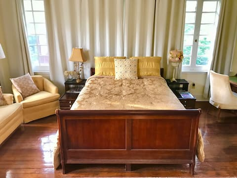 The Treetop Room provides a tranquil space with 16 windows, a queen-size bed, sitting area and desk.