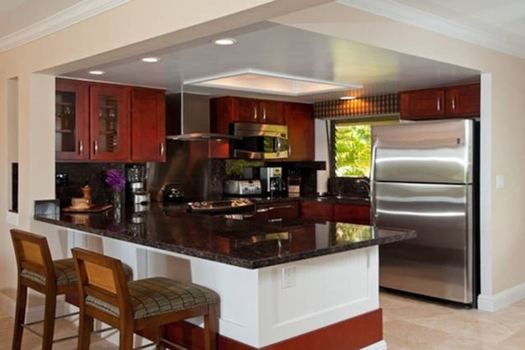 Kitchen with Recessed Lighting, Stainless Steel Appliances and Granite Counters.