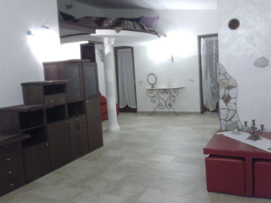 Ambiente particolare con letto mansardato Con scala in legno e tavolinetto