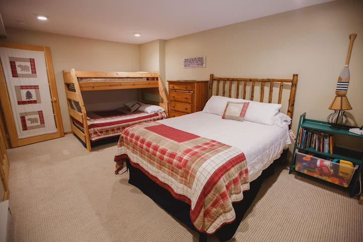 Lower level bedroom with a queen bed, bunk bed with full sized bottom bunk and kids toys and book.