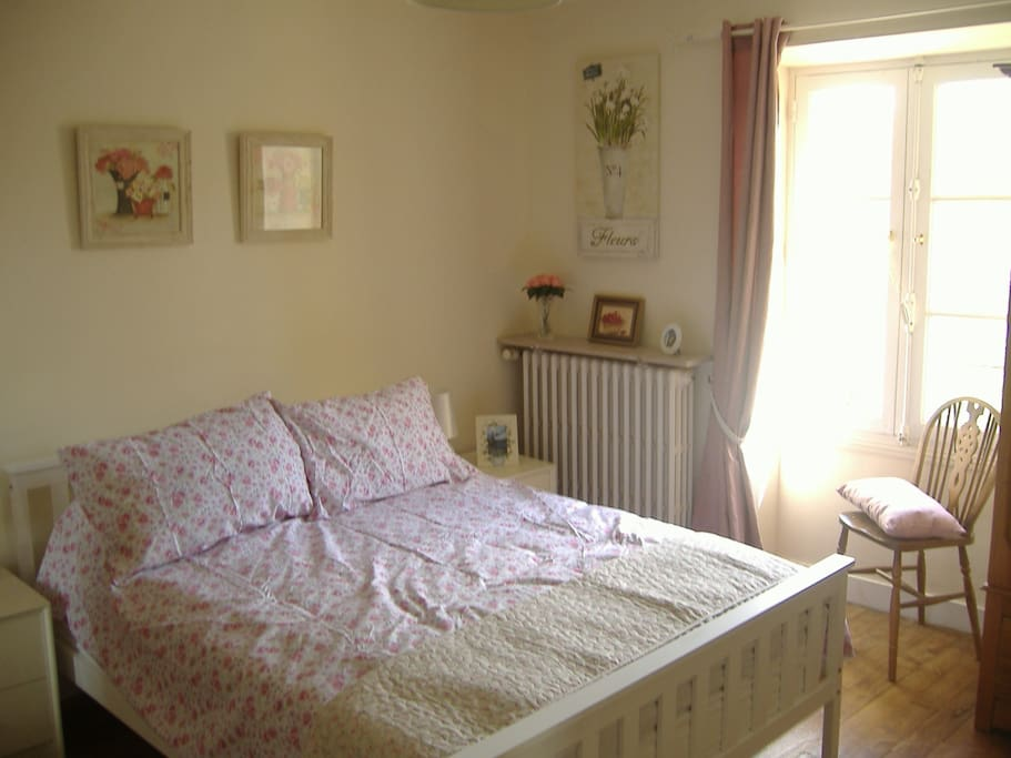 Bright, sunny bedroom with a double bed.