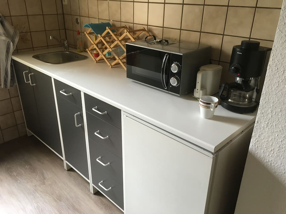kleine Küchenzeile mit Mikrowelle, Wasserkocher und Kaffeemaschine