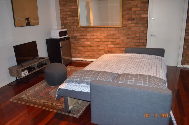 Living room converted to second bedroom with double bed