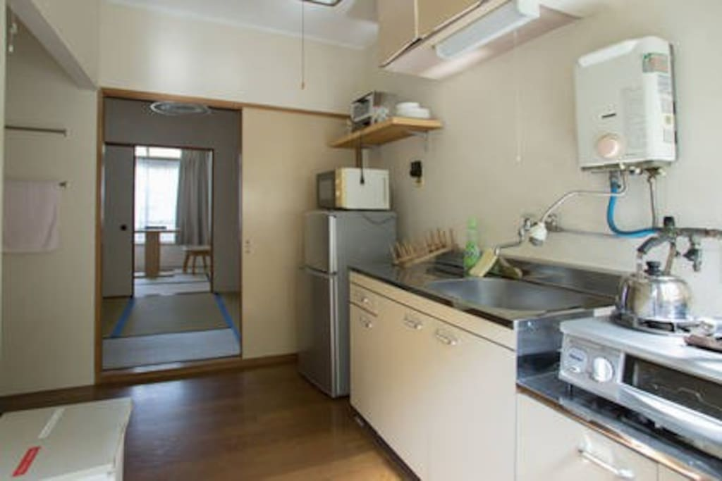 kitchen has refrigerator, toaster, microwave and grill