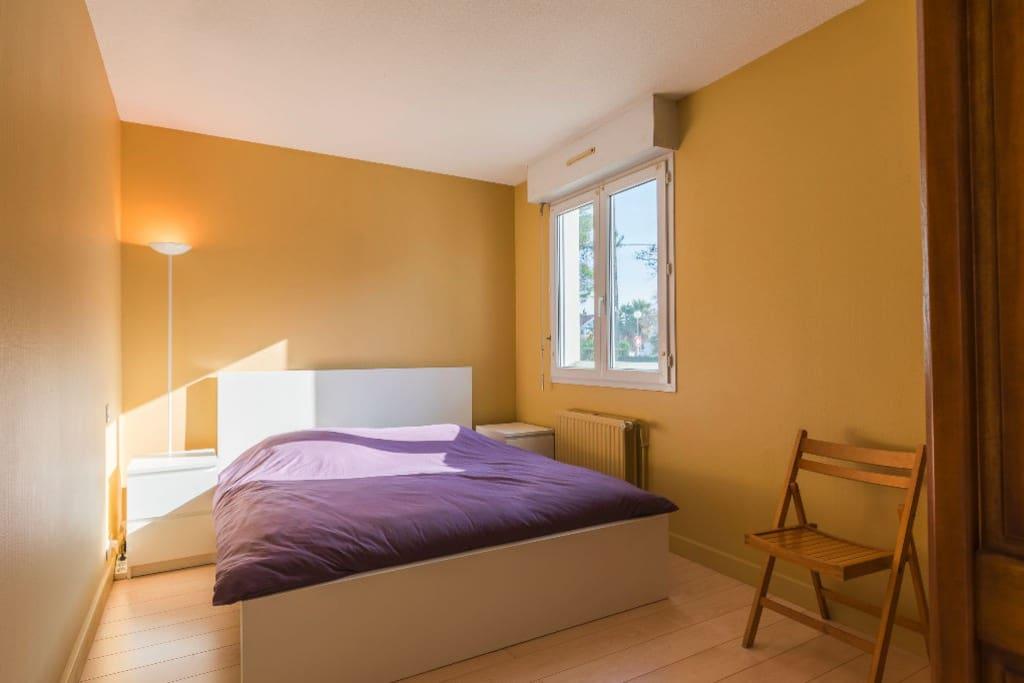 Chambre 1, son lit Queen Size et son armoire donnant sur les espaces verts