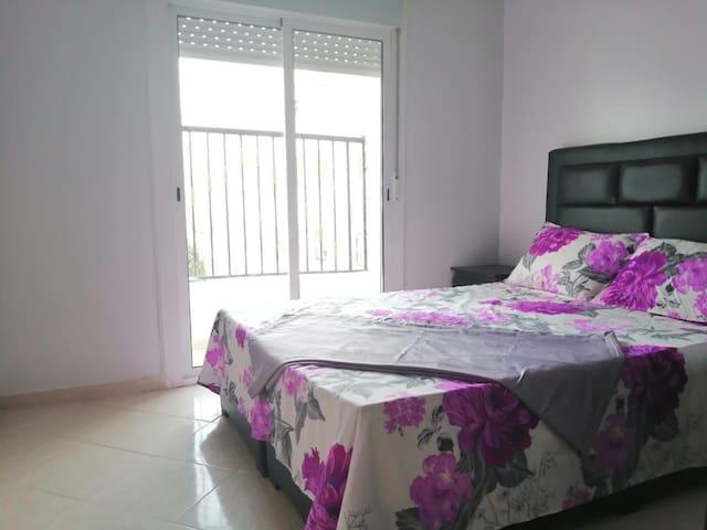 Chambre aérée avec un grand balcon, lit double et placard pour rangement