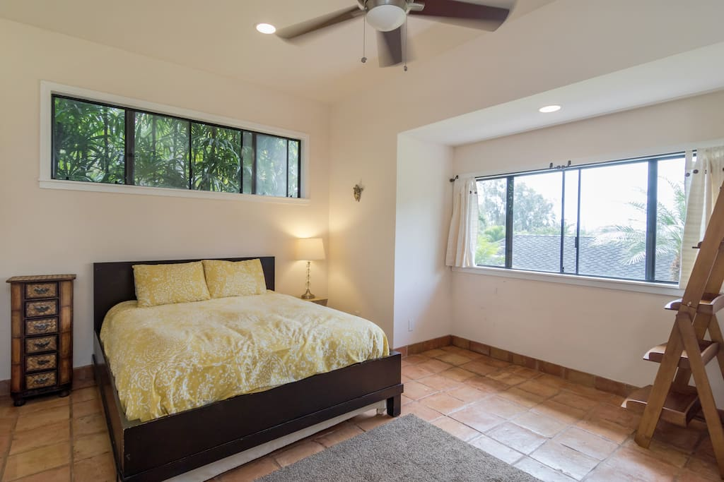 Comfortable and spacious bedroom with high ceilings