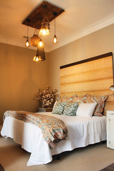 King size bed with fine linens and an industrial headboard made of wood from our farm.