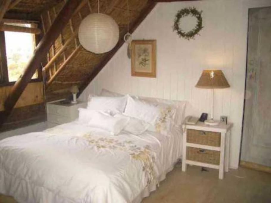 Secluded cozy upstairs bedroom , exposed thatch ceiling, With TV.