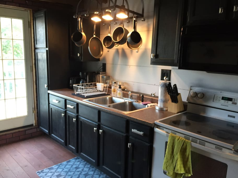 Kitchen is fully equipped, doors lead to a deck
