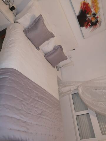 Main bedroom is spacious and bright and modern with air conditioning and ensuite bathroom and walk in shower and hairdryer and towels provided