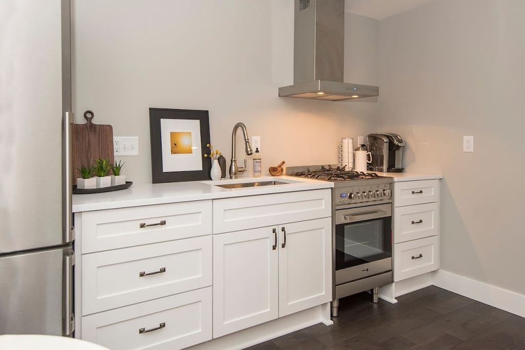 Modern kitchen with quartz counters, soft close cabinets and dual fuel gas range!